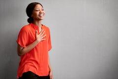 Upptaget skratta för lycklig afrikansk entreprenör med en hand på bröstkorg royaltyfri foto