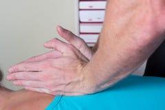 Upptagna behandlande patienter för kiropraktor tillbaka royaltyfri foto