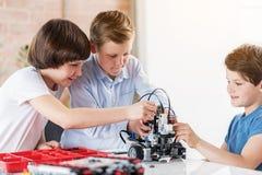 Upptagna intresserade gossebarn som kontrollerar roboten Arkivfoton