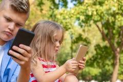 Upptagna ungar som ser deras telefoner som smsar sms och utanför spelar sammanträde arkivbild