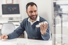 Upptaktbarntekniker som undersöker mycket noggrant den för en tid sedan utskrivavna modellen 3D Arkivbild