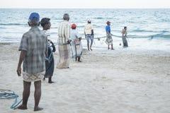 Uppuveli, Sri Lanka - 26 de marzo de 2017: Pescadores locales que tiran en la cuerda del fishernet en la playa Foto de archivo