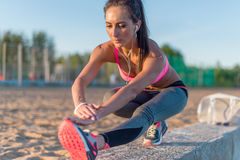 Uppvärmning för flicka för konditionmodellidrottsman nen som sträcker hennes knäsena, ben och baksida Ung kvinna som övar med hör royaltyfri bild