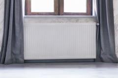 Uppvärmningelement under fönstret med en träram och gardiner arkivfoto