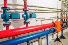 Uppvärmningsystem i ett kokkärlrum röda kraftiga pumpar och blått rörrör Arkivfoton