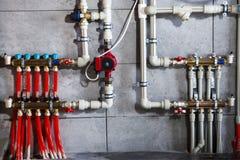 Uppvärmningsystem med plast- rör, ventiler och annan utrustning i kokkärlrummet arkivbild