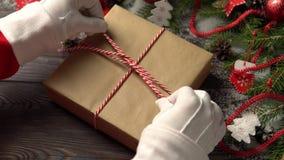Upraw ręki wiąże prezent blisko conifer Santa rozgałęziają się zbiory