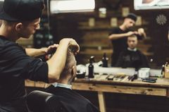 Uprawa fryzjer męski robi ostrzyżeniu dla klienta Zdjęcia Royalty Free
