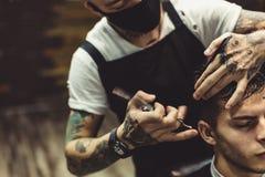 Uprawa fryzjer męski robi ostrzyżeniu dla klienta Fotografia Royalty Free