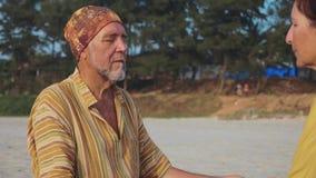 Uprawa starsza para siedzi i medytujący wpólnie na piaskowatej plaży zbiory