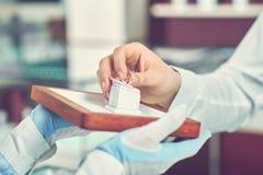 Uprawa trzyma złotego pierścionek wewnątrz męska ręka zdjęcie stock