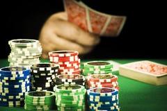 Uprawiać hazard pojęcie, sterta układy scaleni trzyma karty na tle ręka fotografia stock
