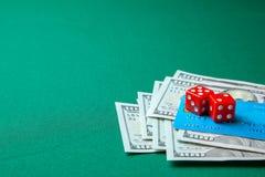 Uprawiać hazard w kasynie Pieniędzy gotówkowi dolary i kredyta wytyczne z kostkami do gry dla gier na zielonym stole fotografia stock