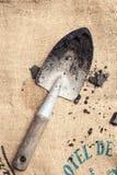 Uprawiać ogródek narzędzie z ziemią na workowym tle Zdjęcia Stock
