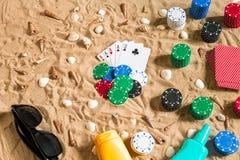 Uprawiający hazard na urlopowym pojęciu - biały piasek z seashells, barwionymi grzebaków układami scalonymi i kartami, Odgórny wi obrazy stock