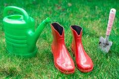 Uprawiający ogródek narzędzie, czerwień ogródu buty, mały rydel, podlewanie puszka na trawie, zamykają up Obraz Stock