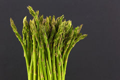 Upright asparagus against black background Royalty Free Stock Images