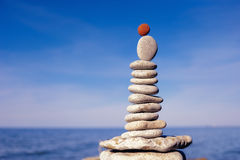 Upright. Balance of red stone on the top of stack of white pebbles Royalty Free Stock Images