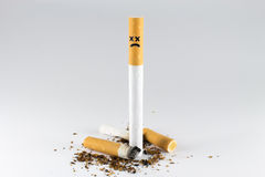 Upright Dead Cigarette!. Cigarette with cross-face/x-face stand above cigarette butts Royalty Free Stock Photos