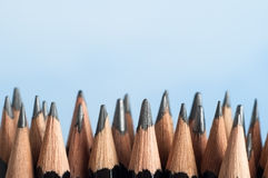 Upright Graphite Pencils. An uneven row of mixed graphite pencils, standing upright against a sky blue background with their tips pointing upwards from the royalty free stock photo