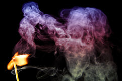 A lit match. Upright lighted matches with clubs and curls of smoke of different colors on a dark background Royalty Free Stock Photo