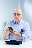 Upright nerdy clerk with two telephones Stock Photos