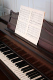 Upright Piano. Some sheet music sits on an antique upright piano Stock Images