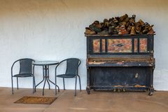 Upright piano with table and chairs. Old upright piano covered in lost shoes near table and chairs Royalty Free Stock Photo