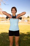 Upright rows. Young woman perfoming upright shoulder rows Stock Photography