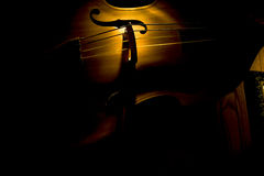 Upright String Bass. Upright acoustic string bass in shadowed lighting.  Instrument is in a horizontal position Stock Image