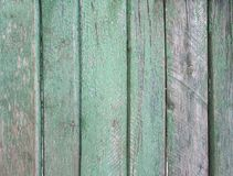 Upright striped wooden wall, fence, background with old threadbare green paint Stock Photography