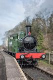 Steam locomotive at a platform. An upright vertical format showing a steam locomotive waiting by the platform at a rural railway station and some coming from the Stock Images