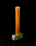 Upright view of a small steel mallet. Upright view of a small steel mallet with a wood handle and green head Royalty Free Stock Image