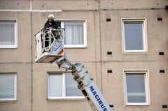 Uprise пожарного в телескопичную корзину заграждения пожарной машины, блока квартир в предпосылке Стоковые Изображения