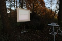 Case of insurance with projection screen. Uprooted tree in a forest with projection screen, beamer and notebook. All equipment is working royalty free stock photos