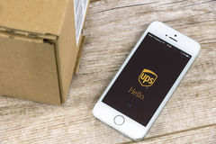UPS app on iPhone. Krynica, Poland - February 10, 2017: UPS tracking shipment app on iPhone SE, close to a parcel post. UPS is one of the largest postal shipping Royalty Free Stock Photo