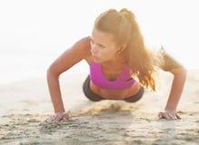 Ups den unga kvinnan för kondition som att göra skjuter, på stranden arkivfoton
