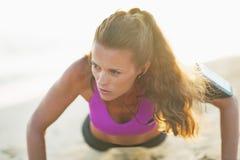 Ups den unga kvinnan för kondition som att göra skjuter, på stranden Royaltyfri Fotografi