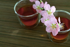 Сups of tea with blossom branch. Сups of tea with blossom pink flowers cherry branch. Selective focus Royalty Free Stock Image