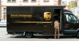 UPS United Parcel Service delivery van with worker driver. KEHL, GERMANY - APR 6, 2017: UPS United Parcel Service van delivery brown UPS van parked on a street Stock Photos