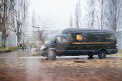 UPS Van on rainy dain delivering mail parcel. PARIS, FRANCE - JAN 4, 2017: UPS United Parcel Service van delivery brown UPS van driving fast on a snowy rainy day Stock Photography