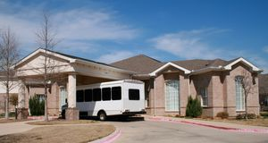 Upscale Assisted Living with Van. Upscale Assisted Living Facility with Transportation Bus waiting outside royalty free stock images