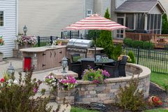 Upscale backyard round brick patio. With outdoor kitchen fitted with a gas barbecue and wicker dining furniture under an umbrella royalty free stock photo