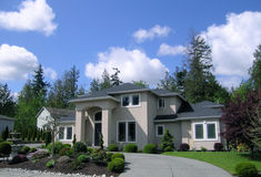 Upscale Home. Luxury House with columns and circular driveway.  Wooded neighborhood Royalty Free Stock Image