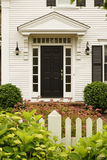 Upscale Home With Landscaping. Front view of an upscale home with a landscaped yard behind a white fence. Vertical shot stock photos