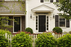 Upscale Home With Landscaping. Front view of an upscale home with a landscaped yard behind a white fence. Horizontal shot stock photo