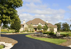 Upscale Home New Paved Driveway. A large luxury home with a new paved driveway and fresh landscaped yard Royalty Free Stock Images