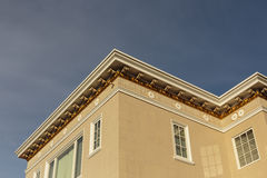 Upscale house roof and cornice detail. Detail of the roof and cornice of an upscale modern home against a blue sky Stock Photo