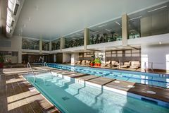 Upscale Indoor swimming pool in condominium complex. Upscale Indoor swimming pool with swim lanes and 2 level gym in condominium complex royalty free stock image