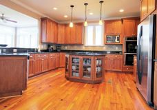 Upscale Kitchen Interior. View of a large upscale kitchen with hardwood floors and modern fixtures. Horizontal format Royalty Free Stock Photography